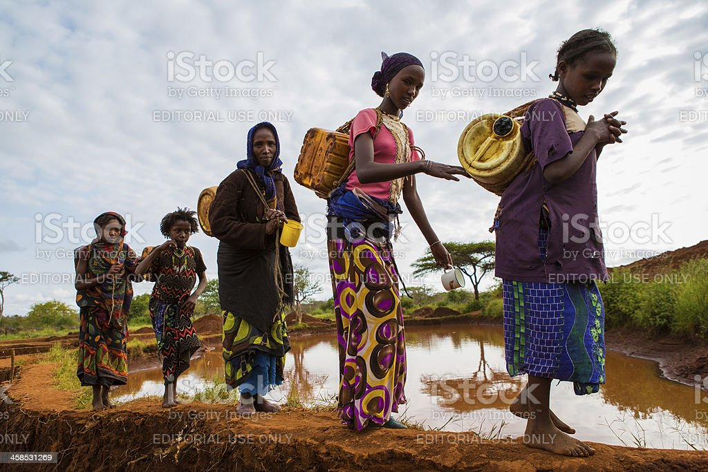 Ethiopian woman and girls with water cans royalty-free stock photo