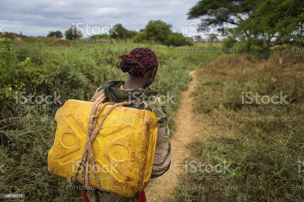 Ethiopian woman carries a can of water from the well royalty-free stock photo
