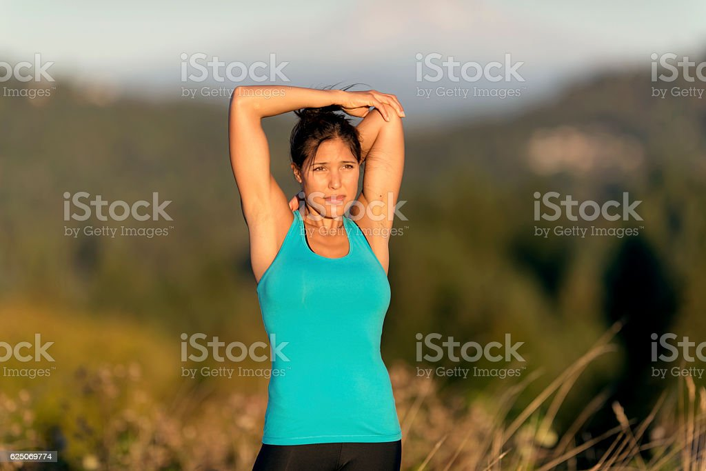 Ethnic adult female athlete stretching arms behind head stock photo