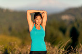 Ethnic adult female athlete stretching arms behind head