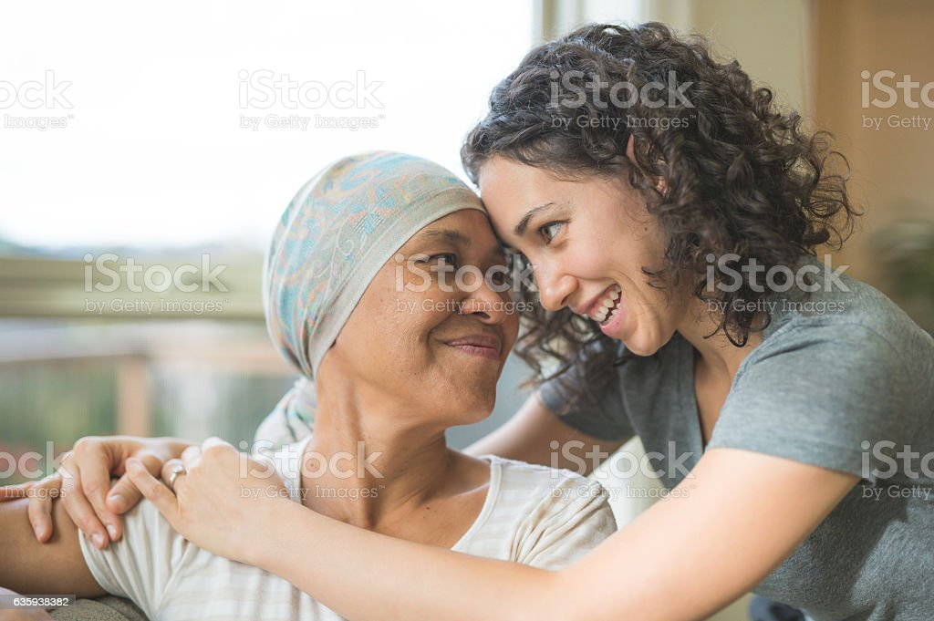 Ethnic adult female cancer patient hugging her daughter stock photo