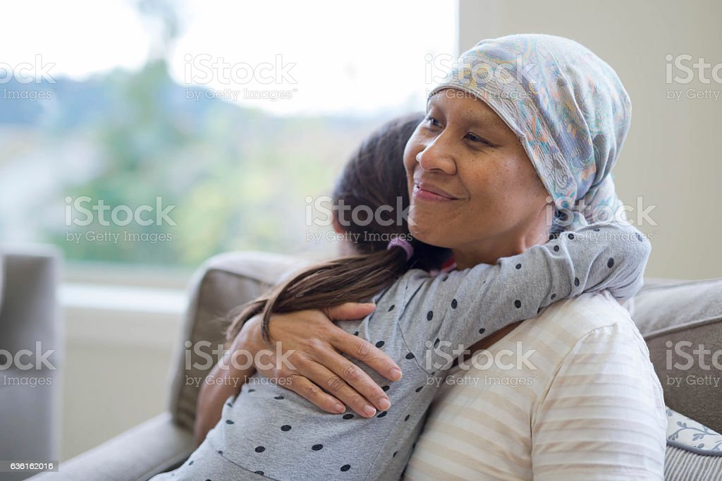 Ethnic adult female cancer patient hugging her granddaughter stock photo
