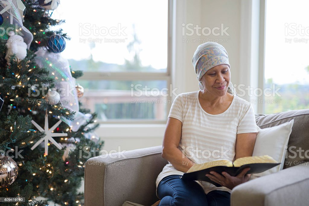 Ethnic adult female cancer patient reading by the Christmas tree stock photo