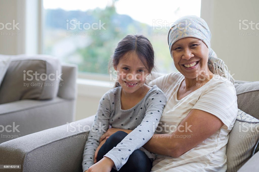 Ethnic adult female cancer patient sitting with her granddaughter stock photo