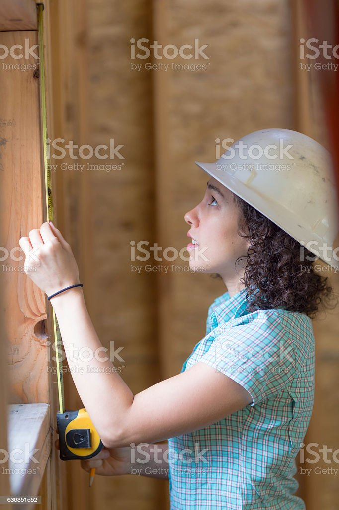 Ethnic adult female measuring a window frame stock photo