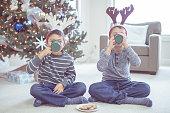 Ethnic boys drinking hot chocolate by the christmas tree