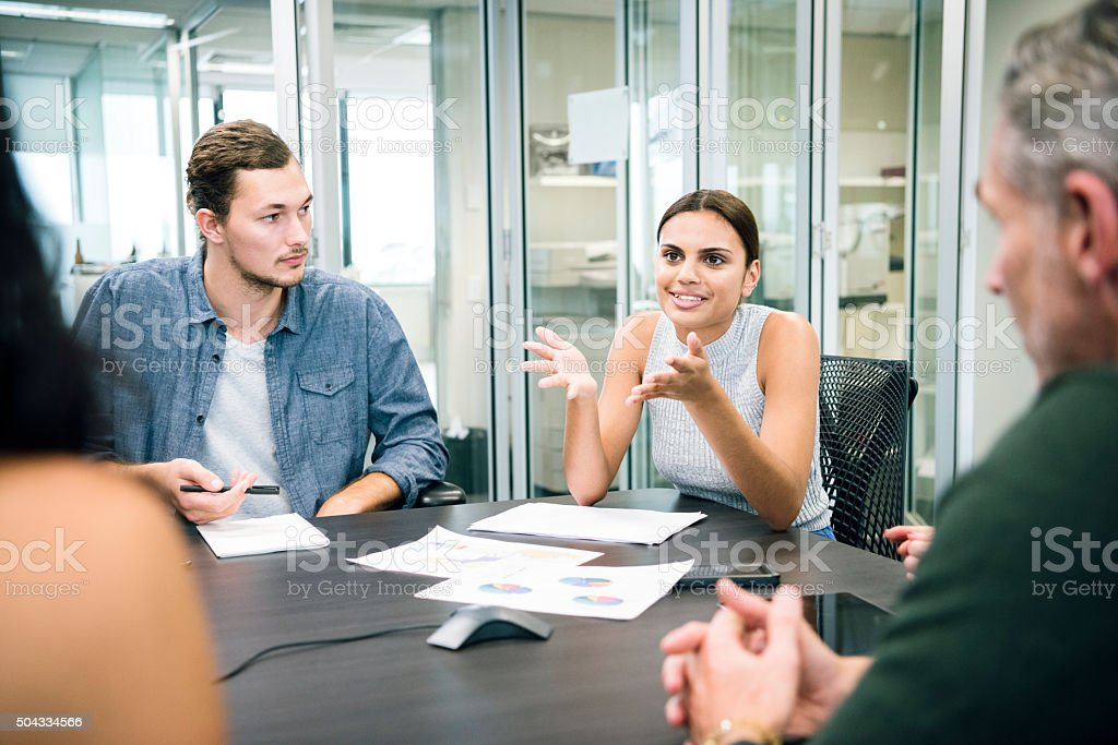 Ethnic businesswoman explaining to colleagues in business meeting stock photo