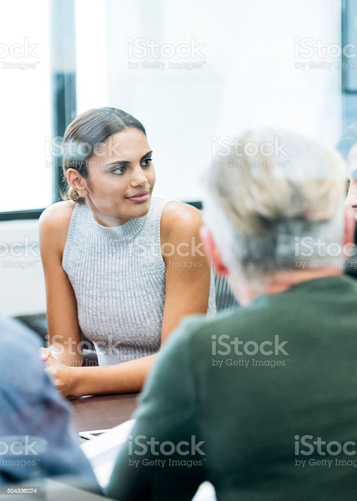 Ethnic businesswoman in business meeting looking away stock photo