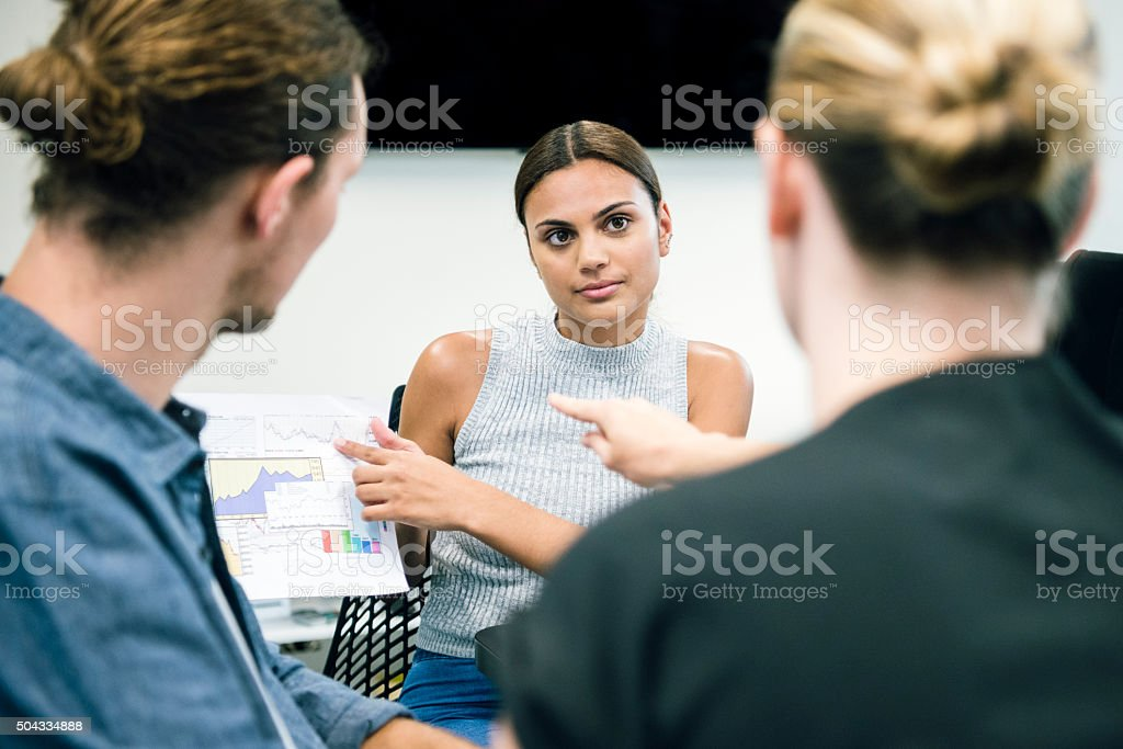Ethnic businesswoman listening to colleagues in business meeting stock photo