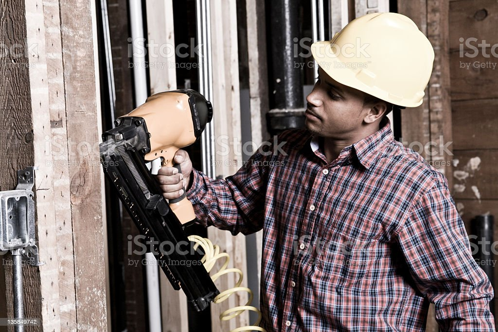 Ethnic construction worker using a nail gun stock photo