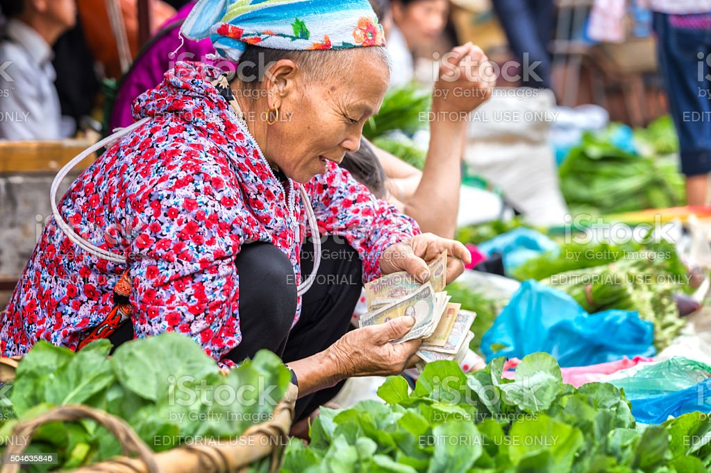 Ethnic counting money selling vegetables at market stock photo