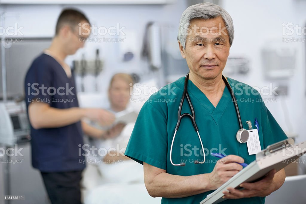 Ethnic Doctor Filling Out Patient Chart stock photo