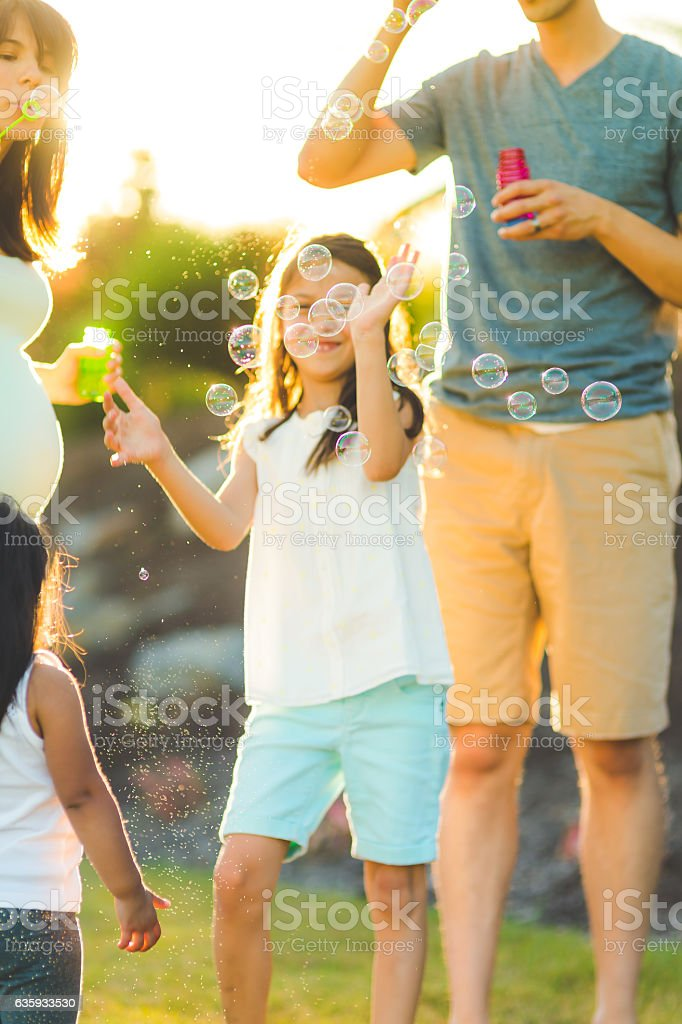 Ethnic family playing with bubbles outside on a warm stock photo