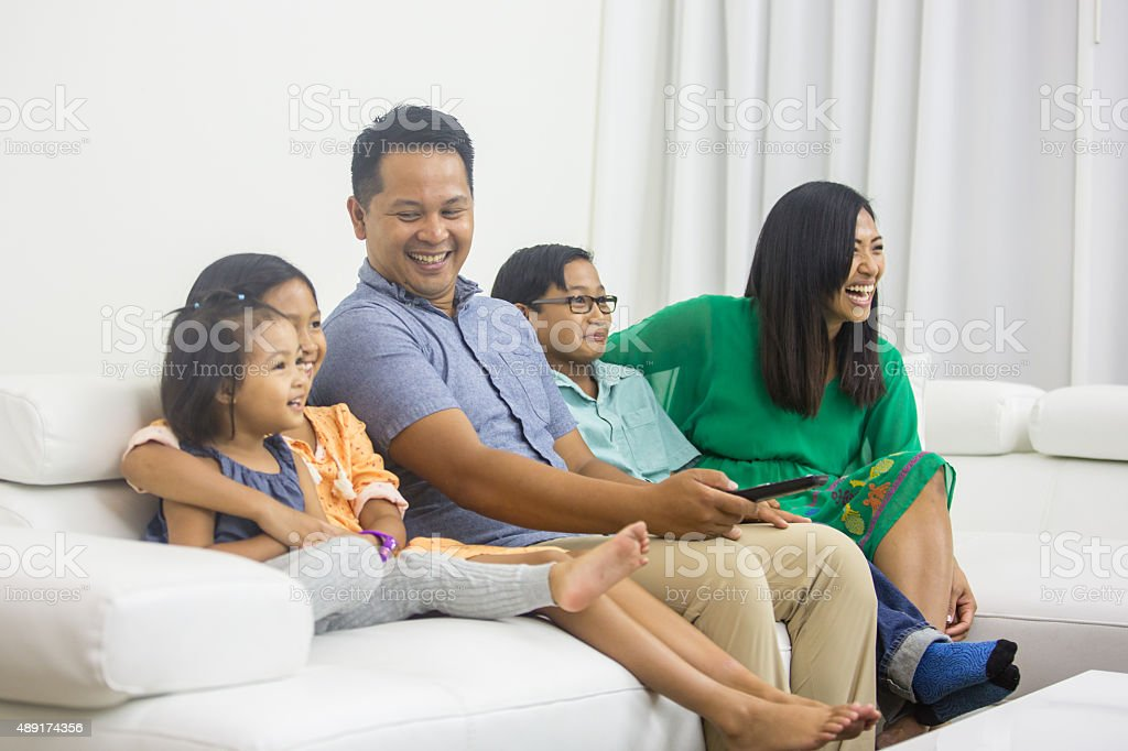 Ethnic family watching television together stock photo