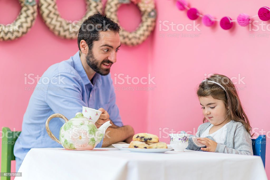 Ethnic father having a conversation with his daughter over tea stock photo