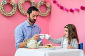 Ethnic father toasting his young daughter during their tea party