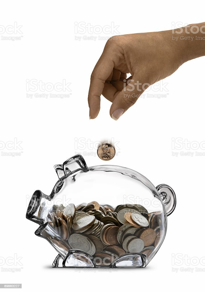 Ethnic Female Hand Drops Coin Into Half-filled Clear Piggy Bank stock photo