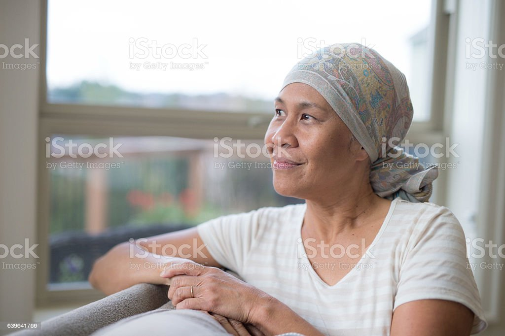 Ethnic female with cancer smiling and looking out the window stock photo