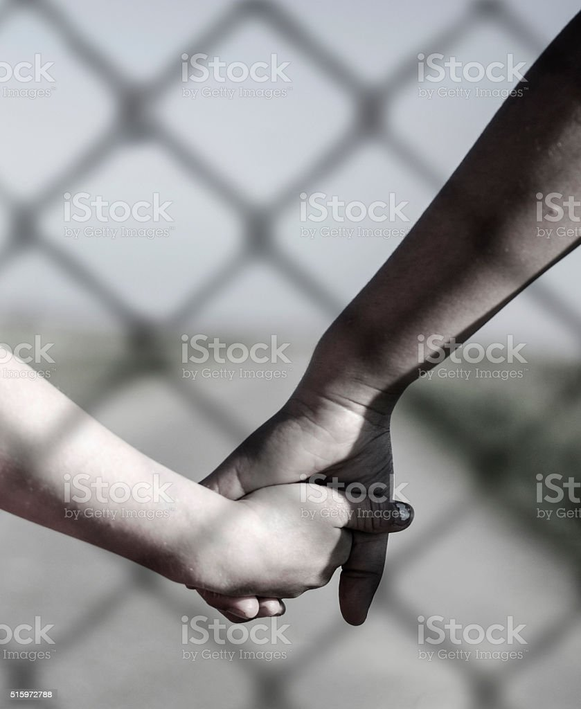Ethnic girl and white girl holding hands behind the fence stock photo