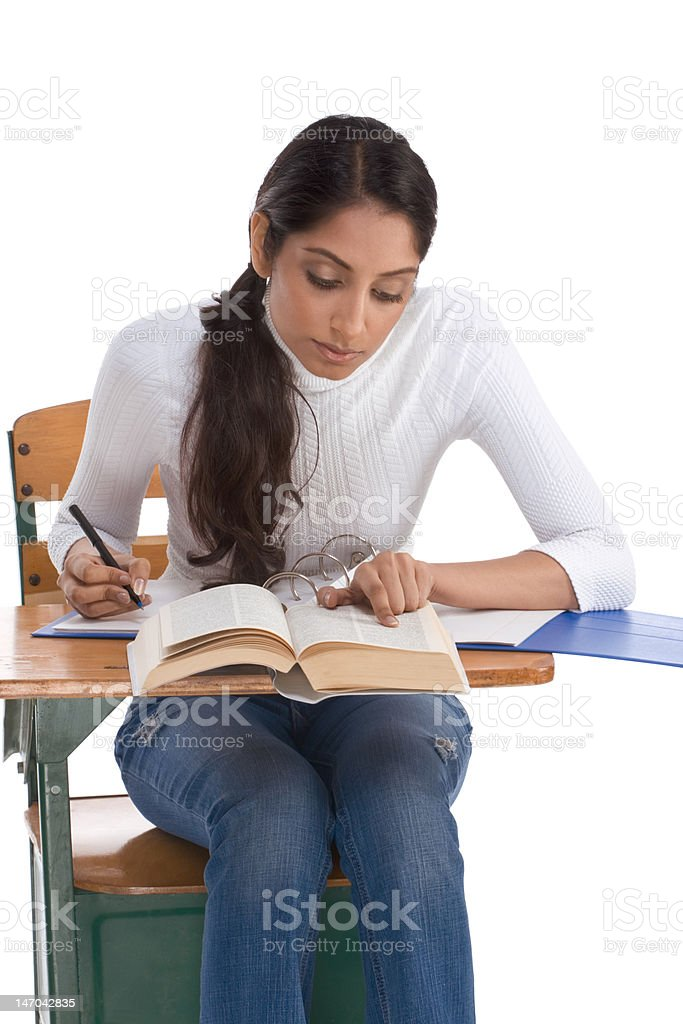 ethnic Indian college student by desk in class stock photo