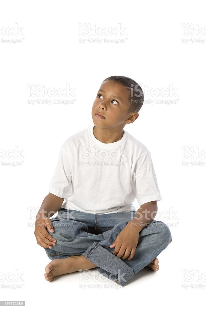 Ethnic Little Boy Sits and Looks Up stock photo
