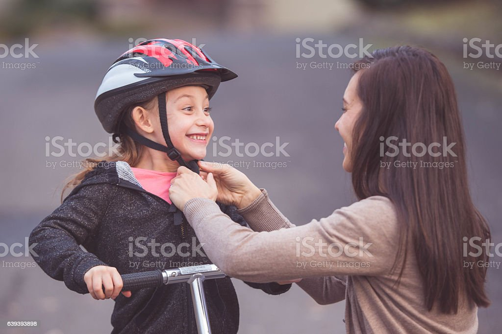 Ethnic mother putting a helmet on her daughter for stock photo