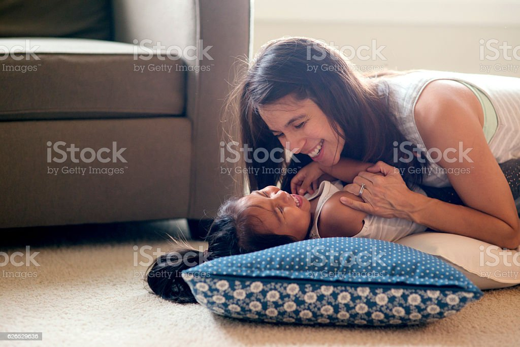 Ethnic mother tickling her cute daughter on the carpeted floor stock photo