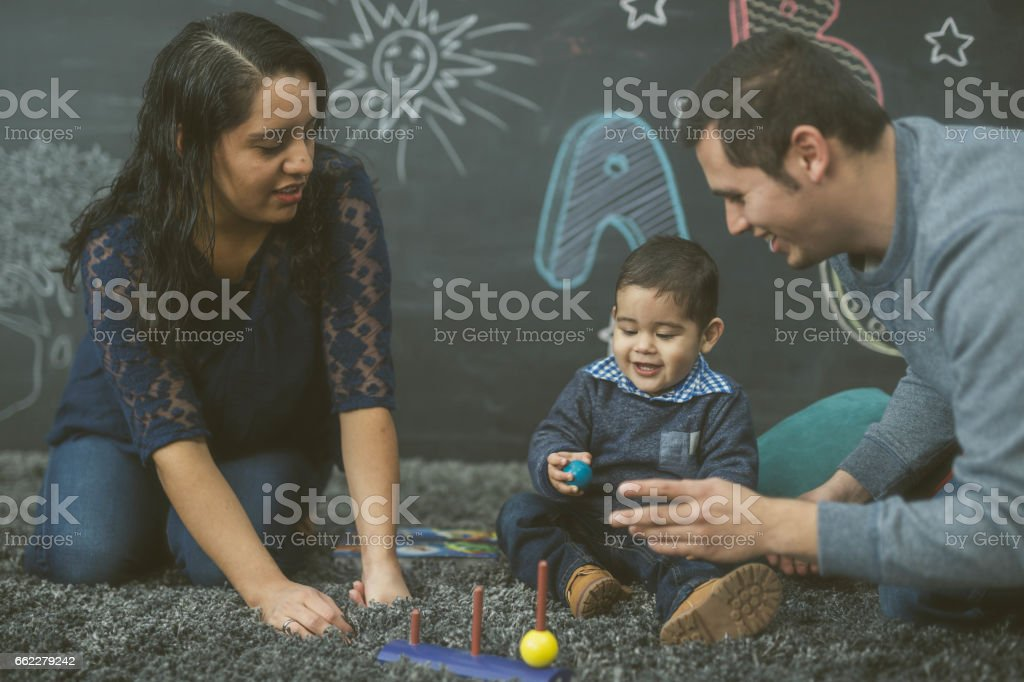 Ethnic parents reading with their toddler in a playroom stock photo