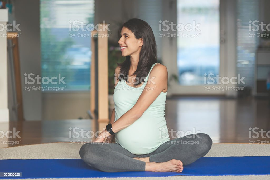 Ethnic pregnant mother doing yoga in the home stock photo