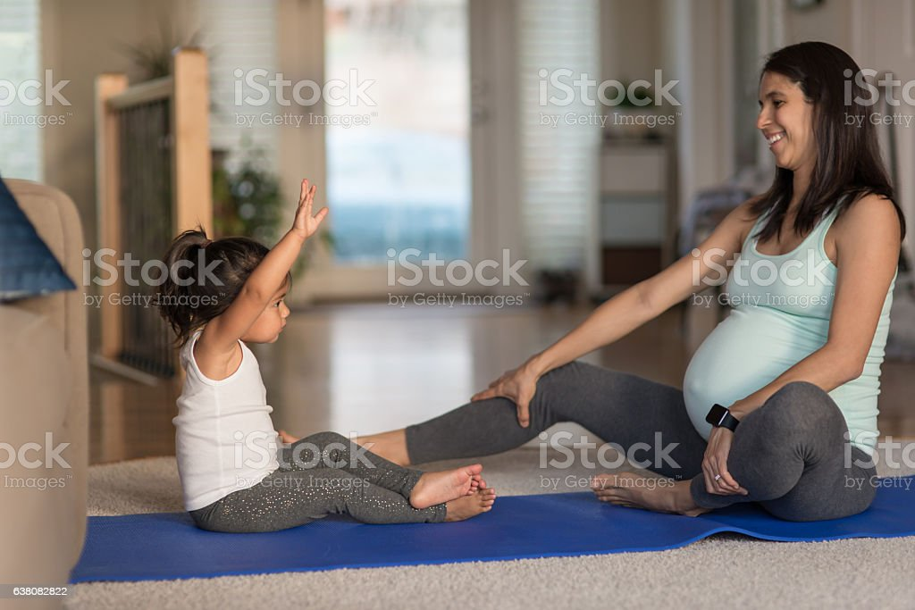 Ethnic pregnant mother doing yoga with her young toddler stock photo