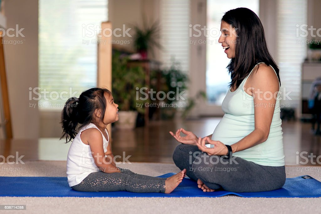 Ethnic pregnant mother meditating with her young daughter watching stock photo