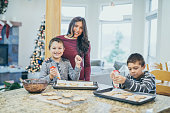 Ethnic single mother making cookies with her two boys