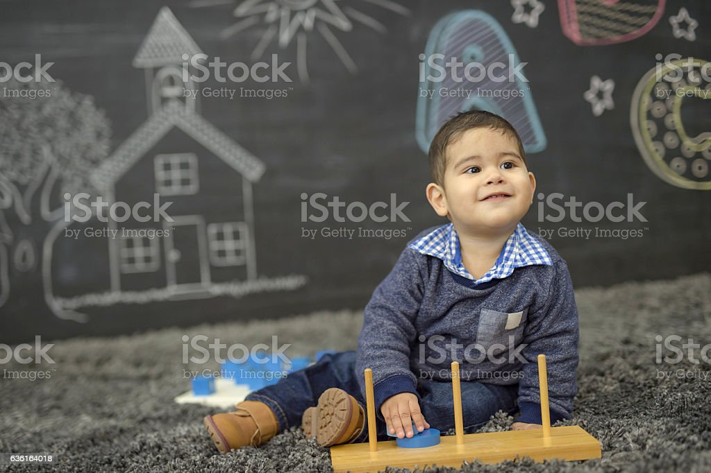 Ethnic toddler playing with his toys in a daycare stock photo
