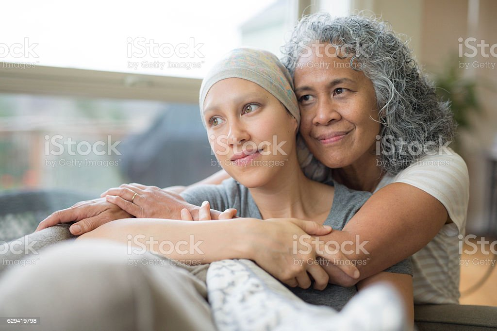 Ethnic young adult female cancer patient hugged by her mother stock photo