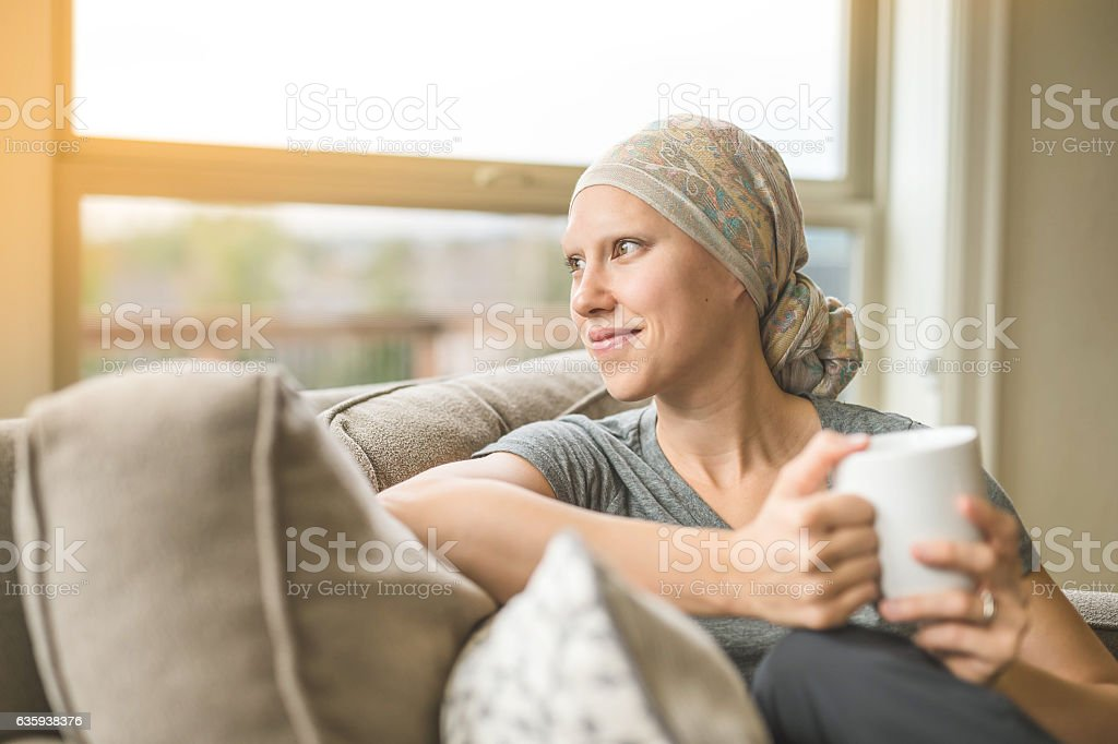 Ethnic young adult female cancer patient sipping tea stock photo