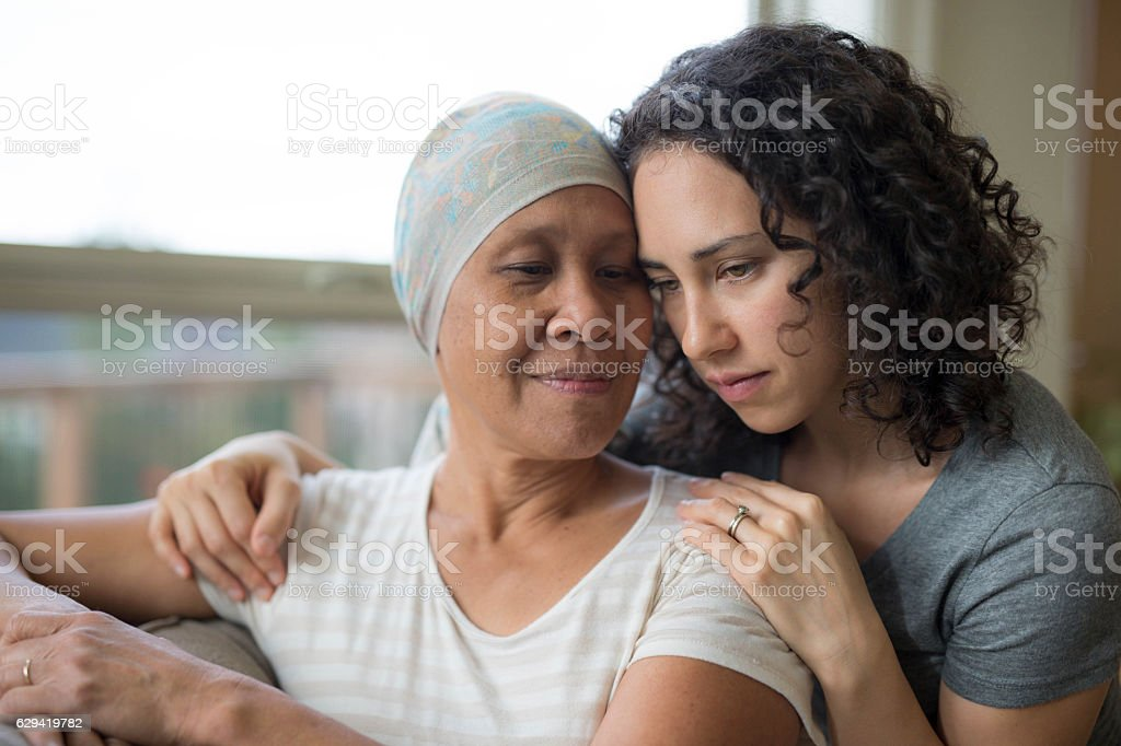 Ethnic young adult female hugging her mother who has cancer stock photo