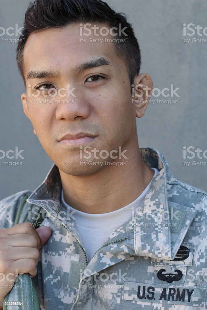 ethnically ambiguous American soldier holding backpack stock photo