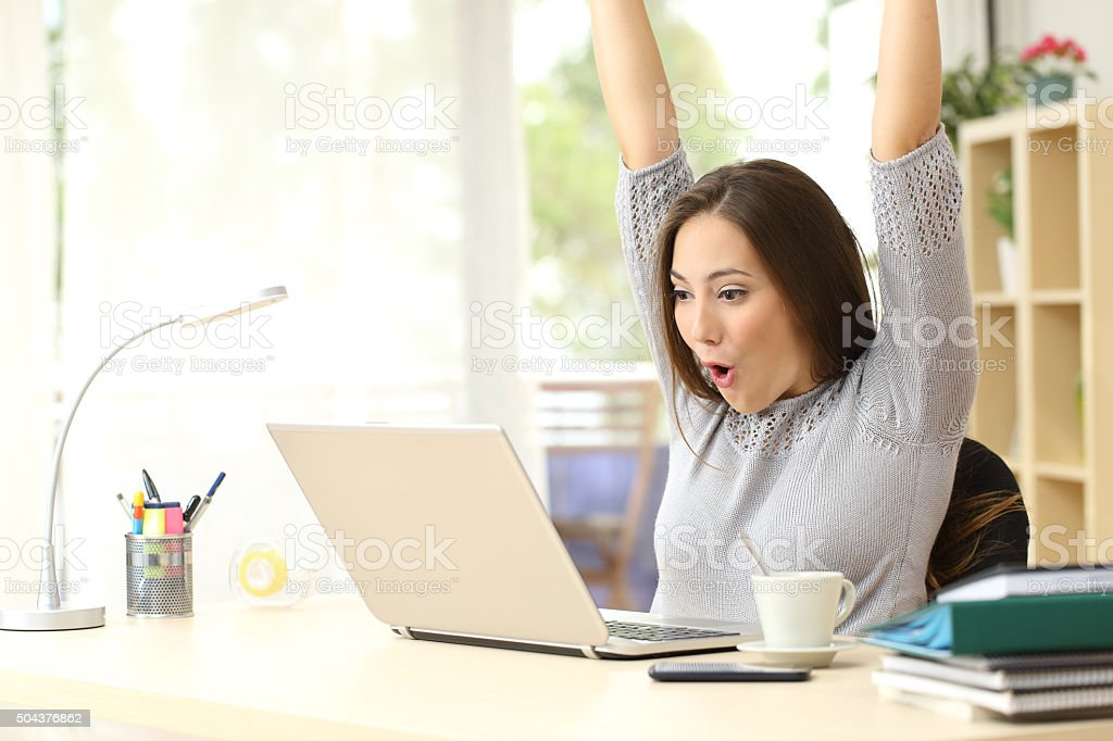 Euphoric and surprised winner winning online stock photo