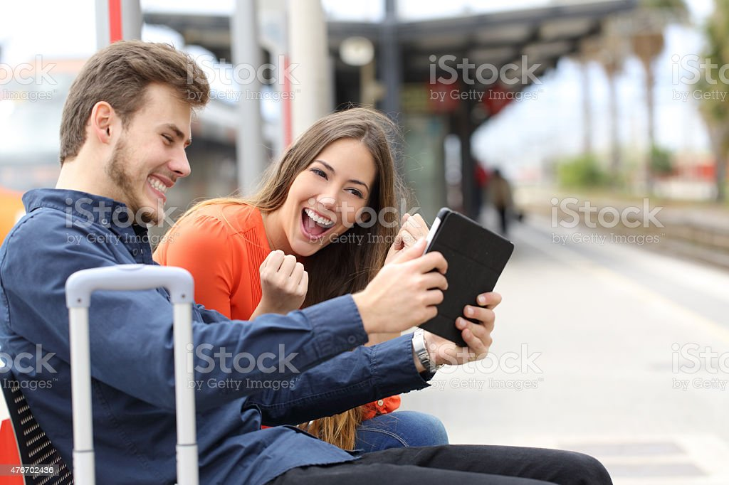 Euphoric couple playing games in a tablet in train station stock photo