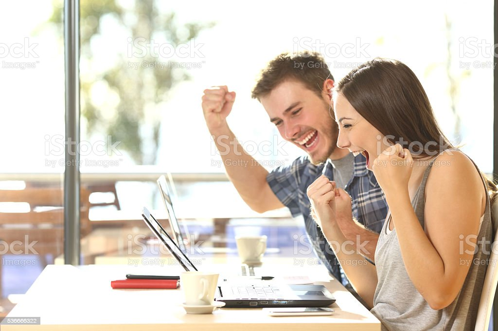 Euphoric students watching exam results stock photo