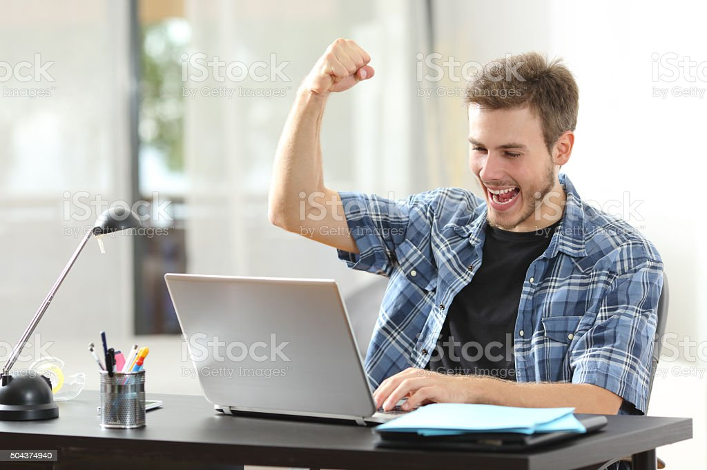 Euphoric winner man using a laptop at home stock photo