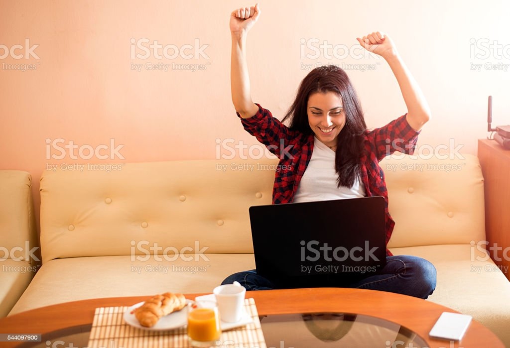 Euphoric winner watching a laptop stock photo