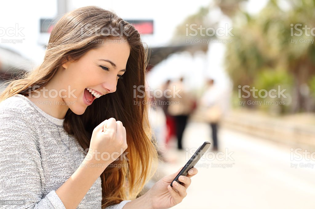 Euphoric woman watching her smart phone in a train station stock photo