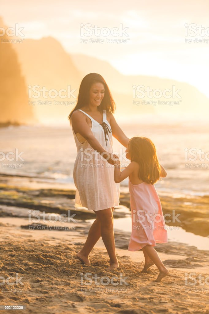 Eurasian mom plays with her young daughter on Hawaii beach stock photo