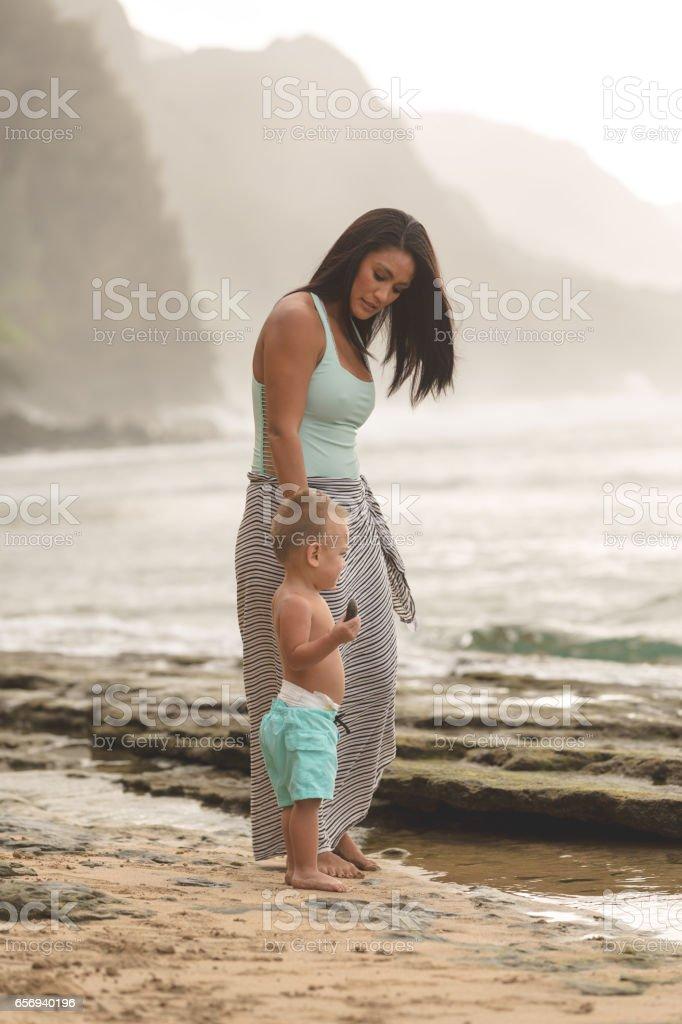 Eurasian mother holding adorable son along sandy Hawaii beach stock photo