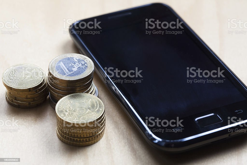 Euro, 50 cent and 20 ct coins with cell phone stock photo
