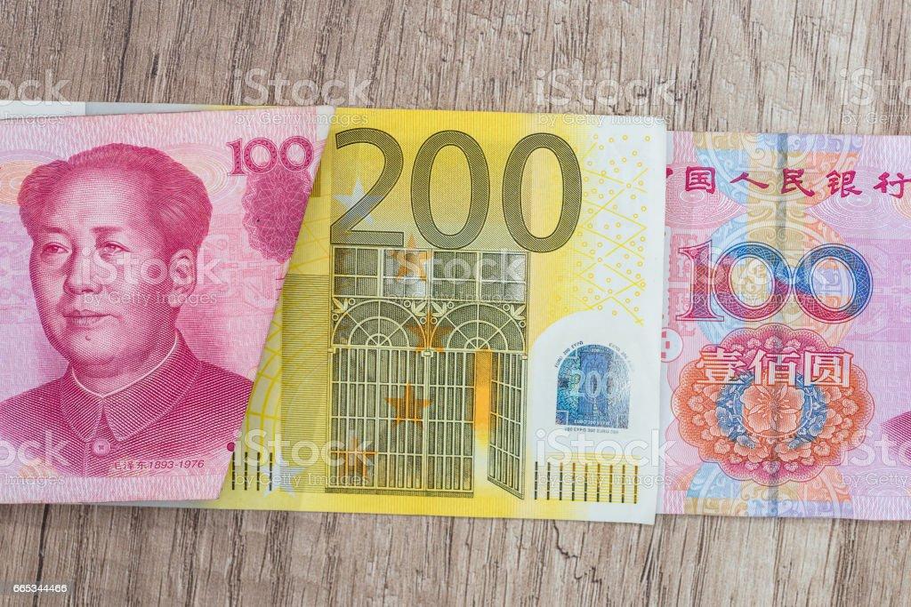 200 euro and 100 yaun bills on desk. stock photo