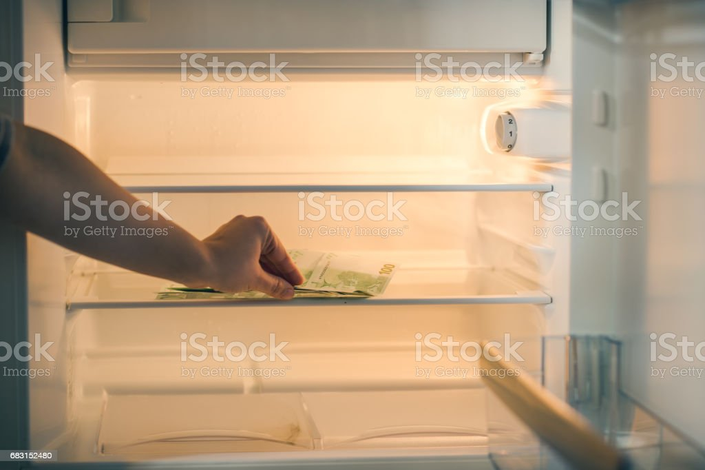 Euro banknotes in an empty refrigerator :a handful of 100 euros banknotes in an empty refrigerator. Female hand take money from fridge stock photo