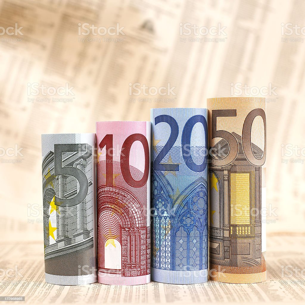 Euro banknotes rolled up on financial newspaper royalty-free stock photo