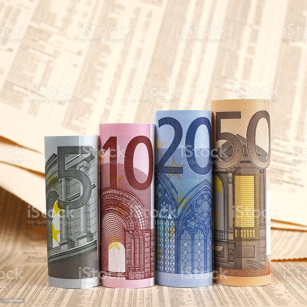 Euro banknotes rolled up on financial newspapers royalty-free stock photo